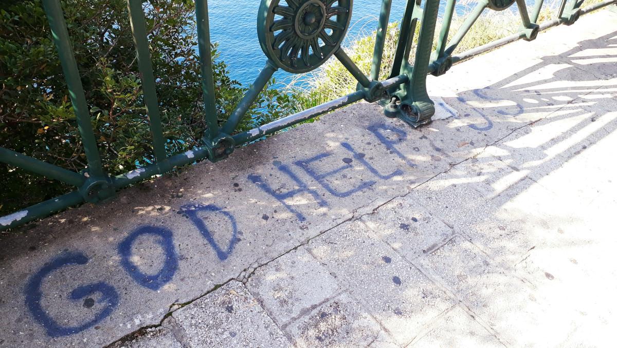 """""""God help us"""" teksti katukivissä"""