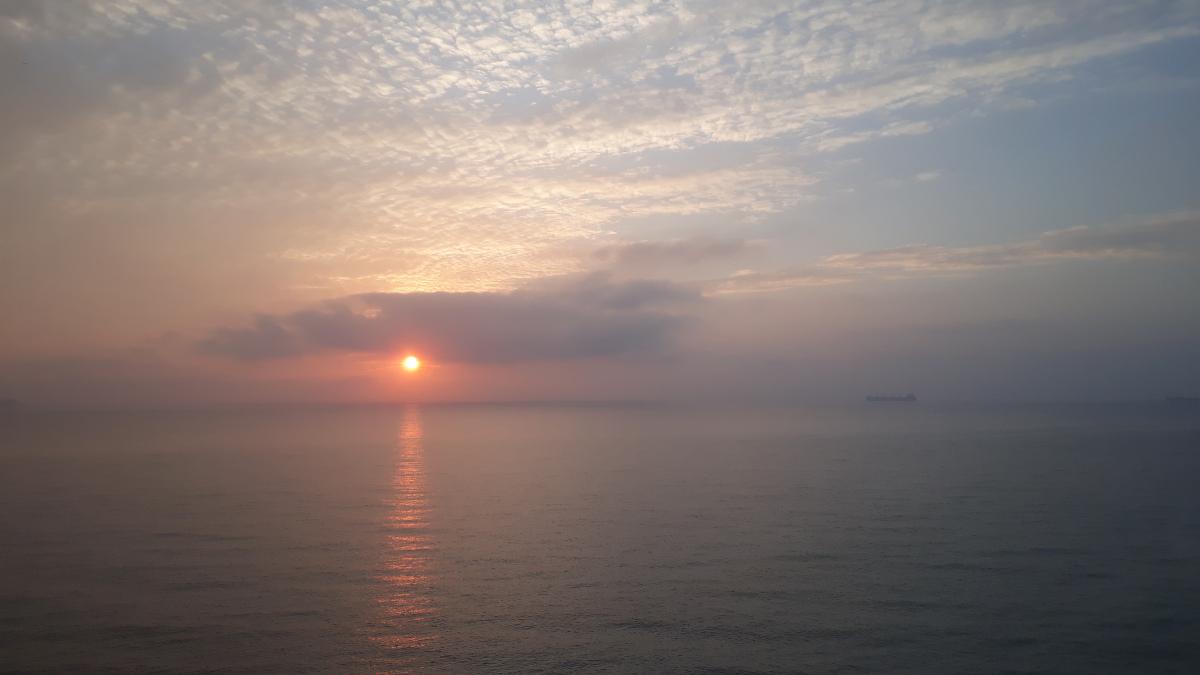 Aurinko laskee järvellä pilven taa