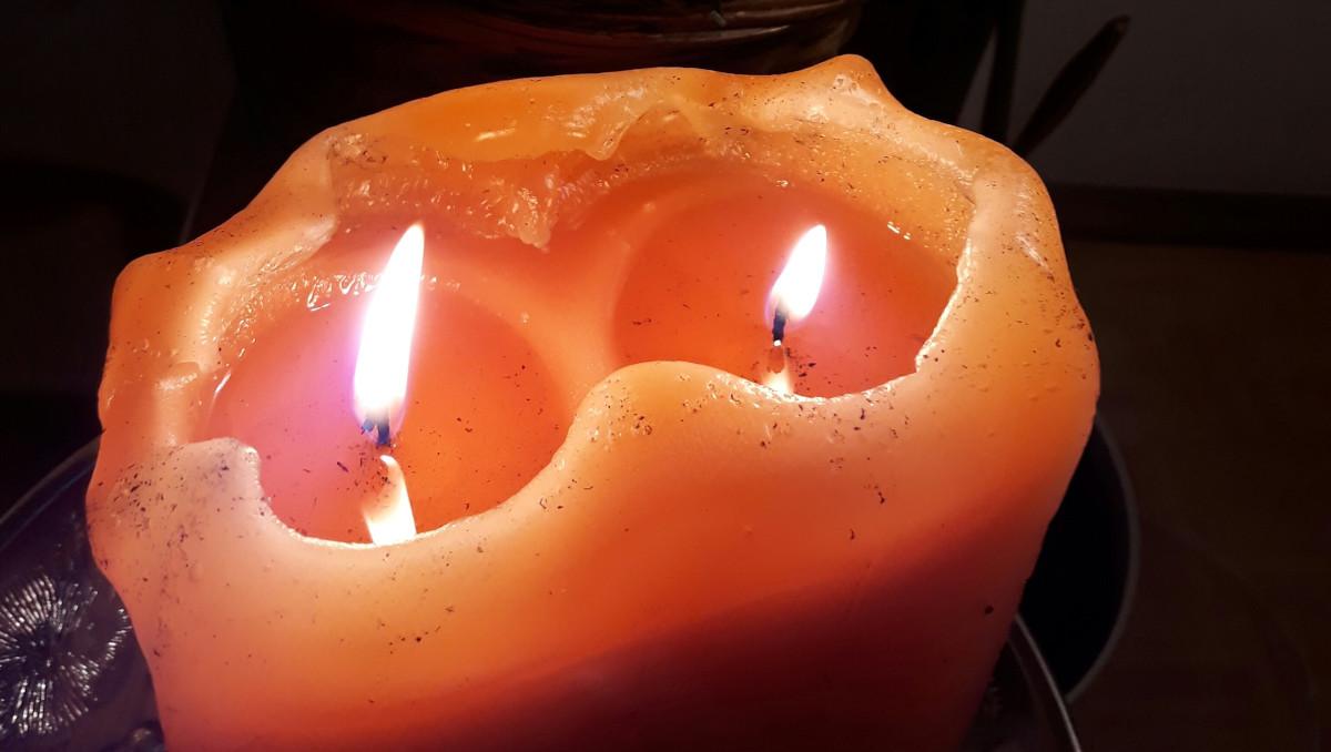 Oranssi kynttilä jossa kaksi sydäntä palamassa
